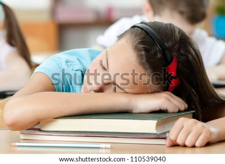 Tired schoolgirl sleeps at the desk, close up - stock photo