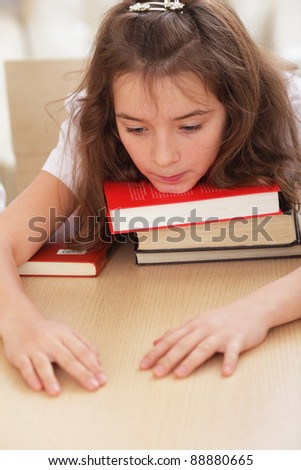 Tired schoolgirl with her chin on books
