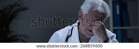 Tired senior general practitioner suffering for depression - stock photo
