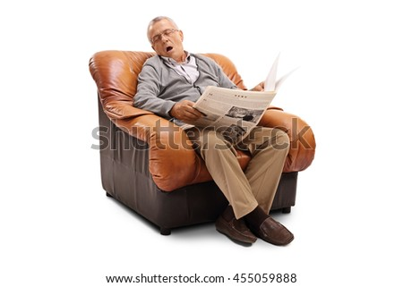 Tired senior gentleman holding a newspaper and sleeping seated on an armchair isolated on white background