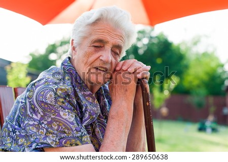 Tired senior woman leaning on her cane - stock photo