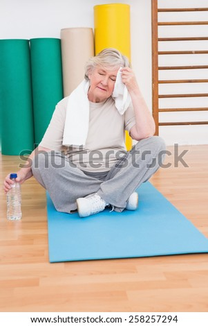 Tired senior woman on exercise mat in fitness mat - stock photo