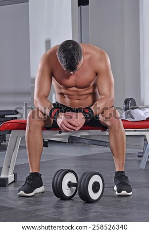 tired sport man taking a rest after training with gym weights. - stock photo