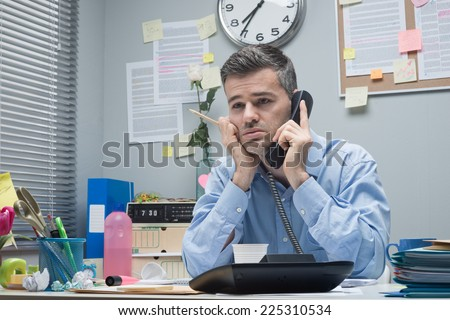 Tired stressed businessman on the phone at his office desk. - stock photo