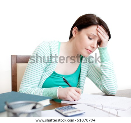 Tired student doing her homework on a desk - stock photo