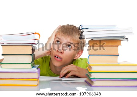 Tired student guy sitting at the desk with pile of books, young man bored study, isolated over white background