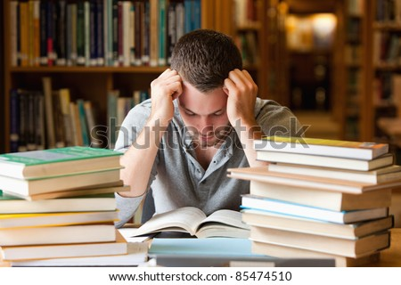 Tired student having a lot to read in a library - stock photo