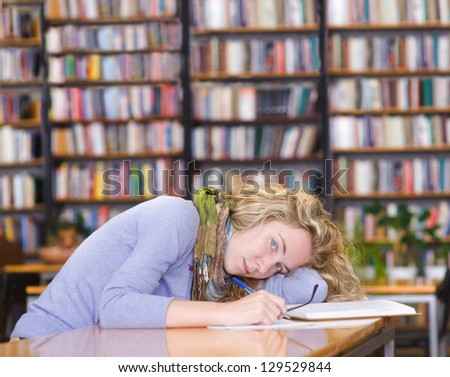 tired student in a university library. looking at camera