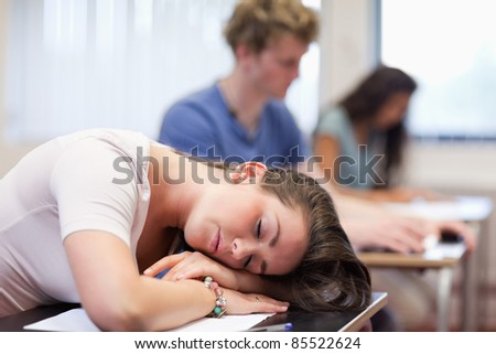 Tired student sleeping in a classroom - stock photo