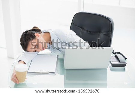 Tired stylish brunette businesswoman sleeping on her desk in bright office - stock photo