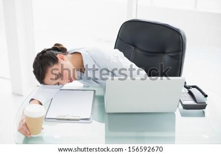 Tired stylish brunette businesswoman sleeping on her desk in bright office - stock photo