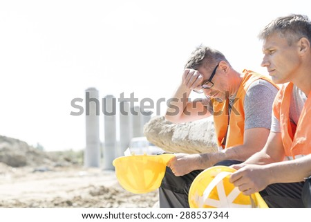 Tired supervisor sitting with colleague at construction site - stock photo