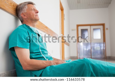 Tired surgeon is sitting on the floor in hospital corridor wearing green scrubs - stock photo