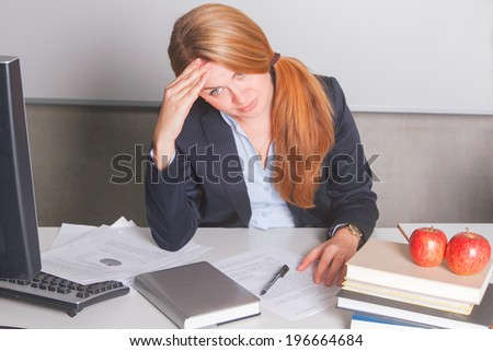 Tired teacher sitting at the table