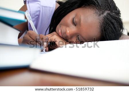 Tired teen girl doing her homework at home - stock photo
