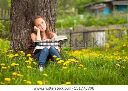 Tired teen-girl in the park with books