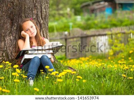 Tired teen-girl with books in the park