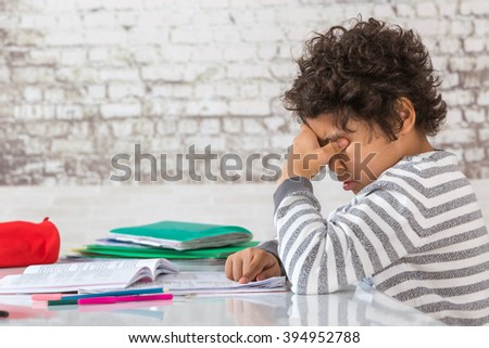Tired Teenager doing Homework at the Home - stock photo