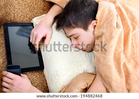 Tired Teenager sleeping at the Home with Tablet Computer - stock photo