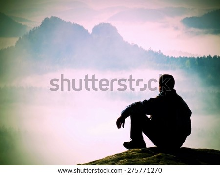 Tired tourist in windcheater and dark cap sit on rock and watching into blue misty valley bellow. Sunny spring daybreak in rocky mountains. - stock photo