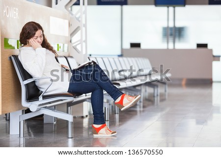 Tired transit passenger sleeping in airport lounge - stock photo