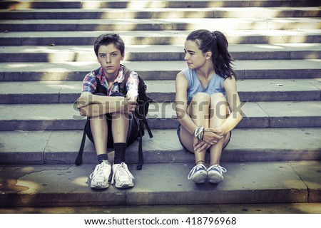 tired travelling siblings sitting on steps - stock photo
