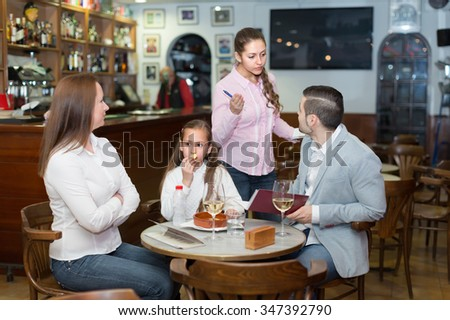 Tired waitress serving displeased family of three at cafe table. Selective focus