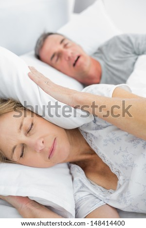 Tired wife blocking her ears from noise of husband snoring in bedroom at home - stock photo