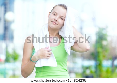 Tired woman after fitness time and exercising in city street park at beautiful summer morning. Sport fitness model caucasian ethnicity training outdoor. - stock photo