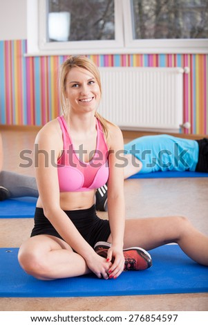Tired woman after workout sitting on exercise mat