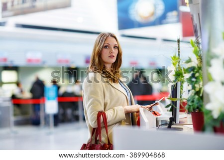 Tired woman at international airport in terminal at check-in desk. Upset, angry female tourist waiting. Canceled flight due to pilot strike. Frankfurt, Germany. - stock photo