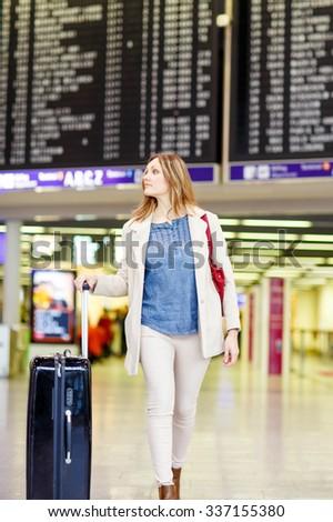 Tired woman at international airport walking through terminal. Angry passenger waiting. Canceled flight due to pilot strike. - stock photo