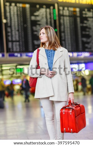 Tired woman at international airport walking through terminal. Upset tourist passenger waiting. Canceled flight due to pilot strike. - stock photo