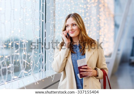 Tired woman at international airport with tickets and passport checking mobile for flight. Upset passenger waiting. Canceled flight due to pilot strike. - stock photo