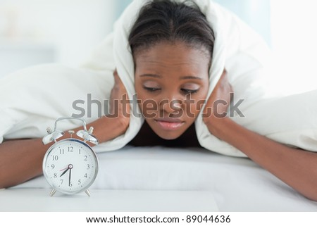 Tired woman covering her ears with a duvet while looking at her alarm clock - stock photo