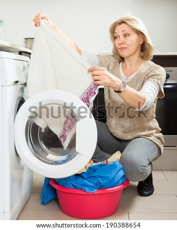 tired woman doing laundry with washing machine at home kitchen - stock photo
