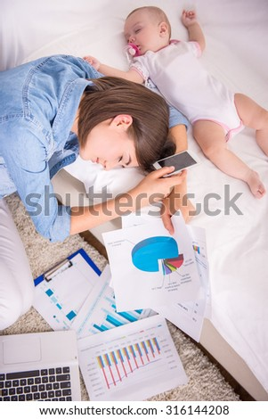 Tired woman falling asleep while working at home and her little baby is sleeping near. - stock photo