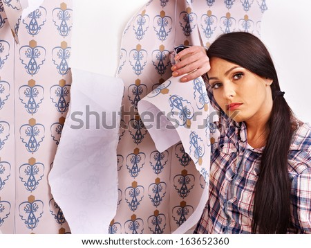 Tired woman glues wallpaper at home. - stock photo