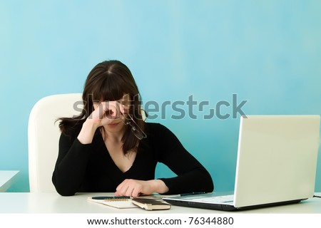 Tired woman in office on a blue  background