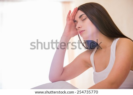 Tired woman is sleeping while sitting on a bed.