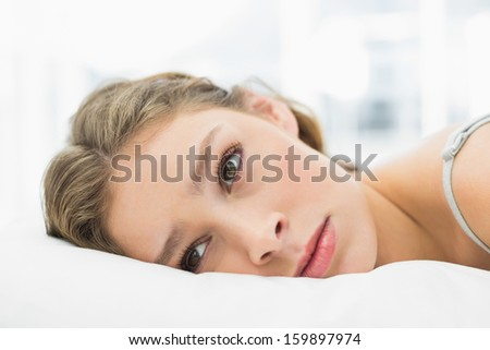 Tired woman lying in her bed looking irritated at home