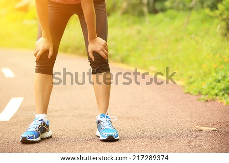tired woman runner taking a rest after running hard in countryside road. sweaty athlete after marathon training in country road.  - stock photo