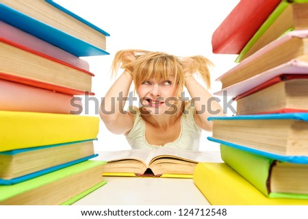 Tired woman sitting at the desk surrounded with piles of books