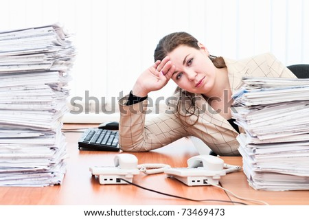Tired woman sitting at the table in working place in office room - stock photo