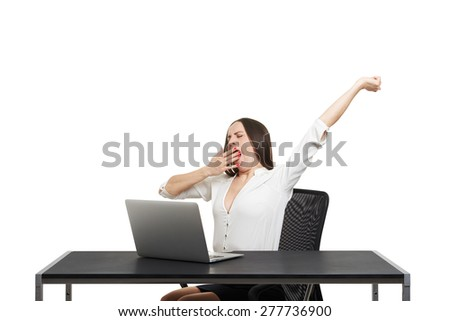 tired woman sitting with laptop and yawning over white background - stock photo