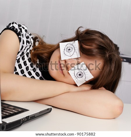 Tired woman sleep in office on desk near computer. She made a fake eyes.