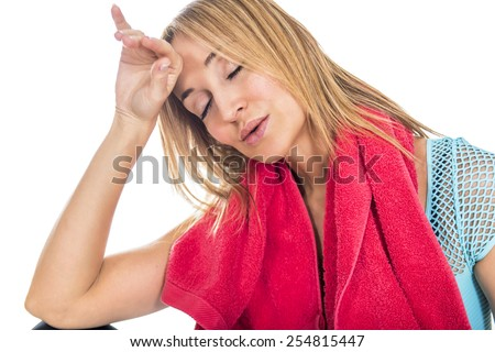 Tired woman wiping sweat off forehead after workout