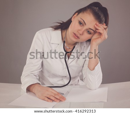 Tired woman with a lot of papers at the table