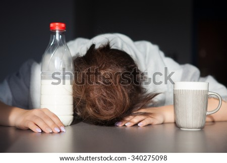 Tired woman with head on the table. Health issue, hangover or Monday morning concept. - stock photo