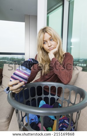 Tired woman with laundry basket sitting on sofa at home - stock photo